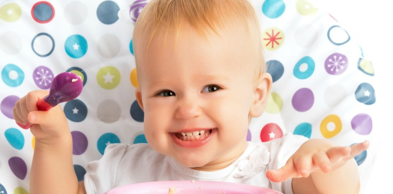 cheerful-happy-baby-child-eats-itself-with-a-spoon
