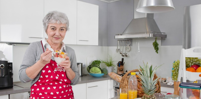 Older happy woman eating yoghurt in the morning with fresh fruits.