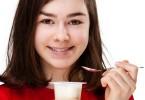 teenage girl eating yogurt