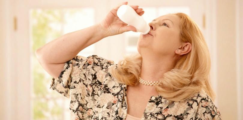 Senior woman standing in kitchen, drinking yogurt in bright background.