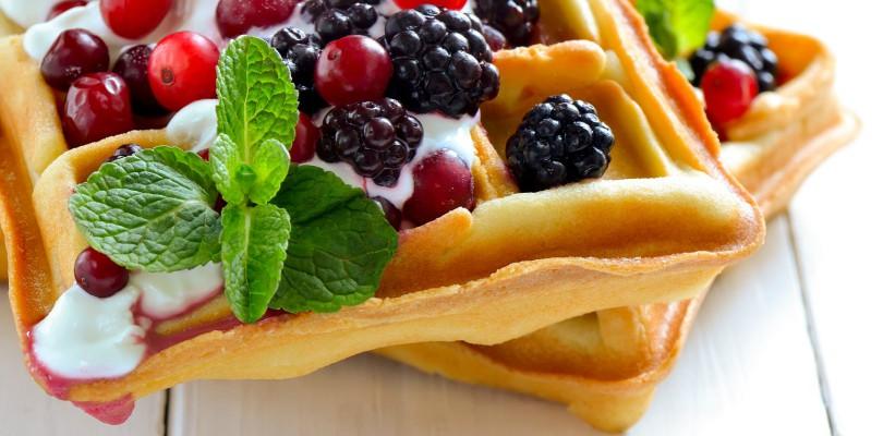 Breakfast with freshly baked belgian waffles with yogurt and berries
